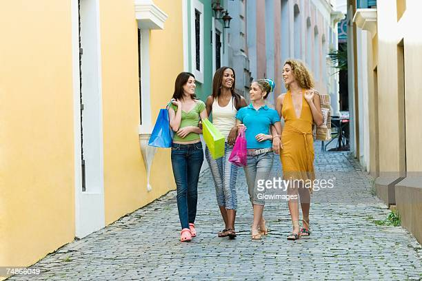 four teenage girls walking in an alley and holding shopping bags - girl wear jeans and flip flops stock photos and pictures