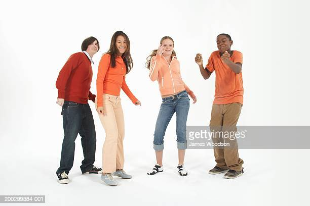 Four teenagers (14-16) dancing against white background, portrait