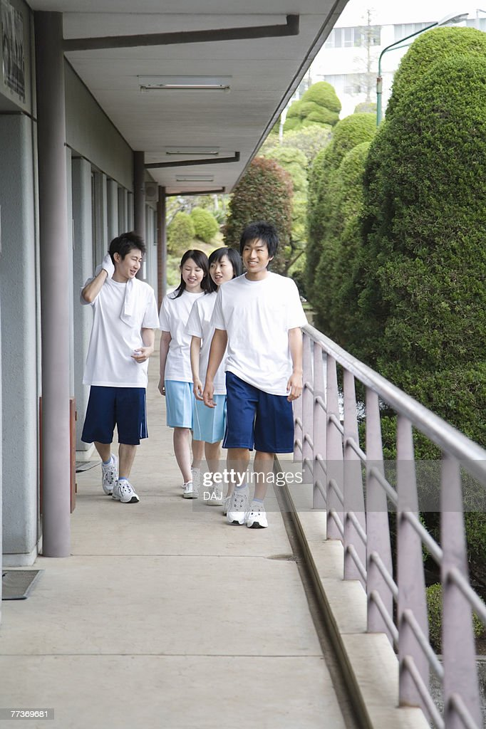 Four teenagers in gym clothes walking at outside corridor : Photo