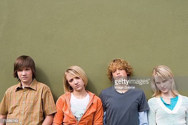 Four teenagers leaning against wall