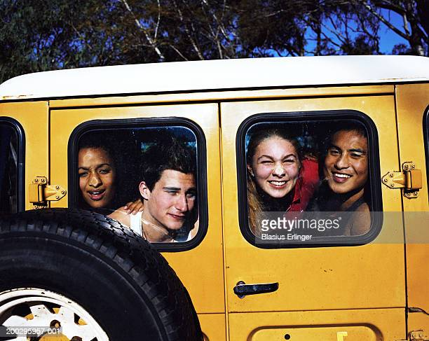 Four teenagers (16-20) looking through vehicle window, portrait