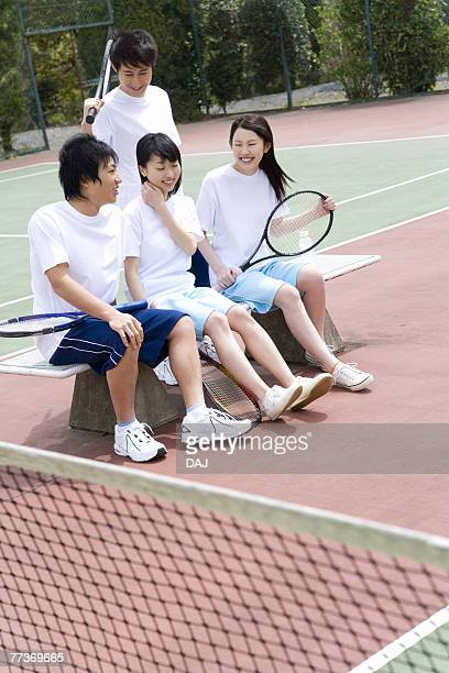 Four teenagers sitting on bench in tennis court, holding rackets