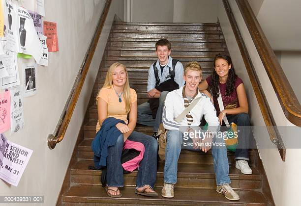 four teenagers (16-18) sitting on stairway in school, portrait - bulletin board flyer stock pictures, royalty-free photos & images