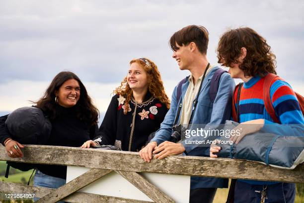 four teens laughing and sharing a joke at a farm gate in the country - outdoor pursuit stock pictures, royalty-free photos & images