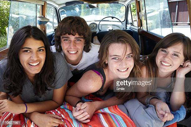 Four teens lying in the back of estate car