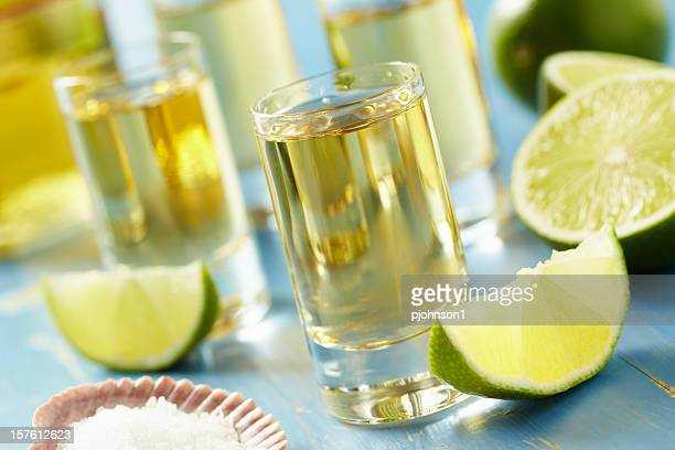 Four tequila shots with lime and salt on a blue table
