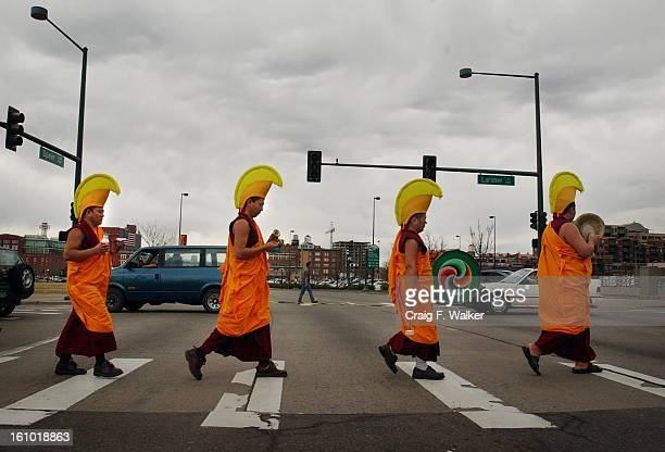 Four Tibetan Lamas of Drepung Loseling Monastery, in India, cross Speer Blvd carrying the sand from a sand-painted mandala they created at the Tivoli...