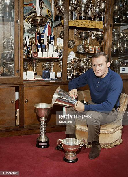 Four time 500cc Motorcycle Racing World Champion Mike Hailwood poses with his many trophies, Oxford, 1965.