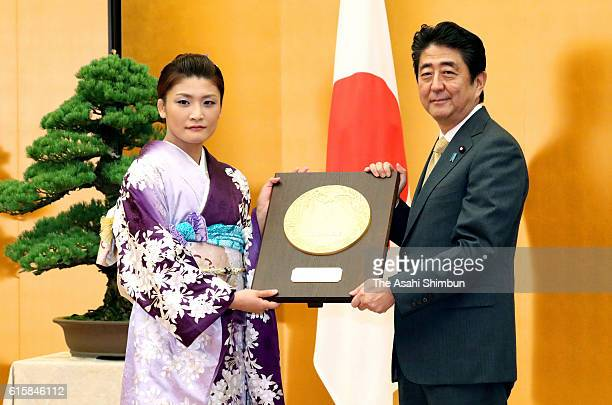 Four time Olympic gold medalist Kaori Icho reaceives the plaque from Japanese Prime Minister Shinzo Abe during the People's Honour Award ceremony at...