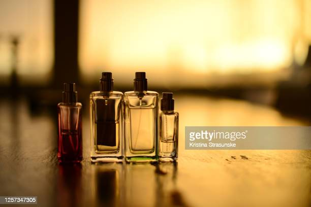 four transparent perfume bottles on a black table, seen in a beautiful golden sunset light - kristina strasunske stock pictures, royalty-free photos & images