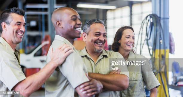 four trucking company workers in garage - manual worker stock pictures, royalty-free photos & images