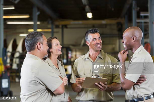 four trucking company workers in garage - stereotypically working class stock pictures, royalty-free photos & images
