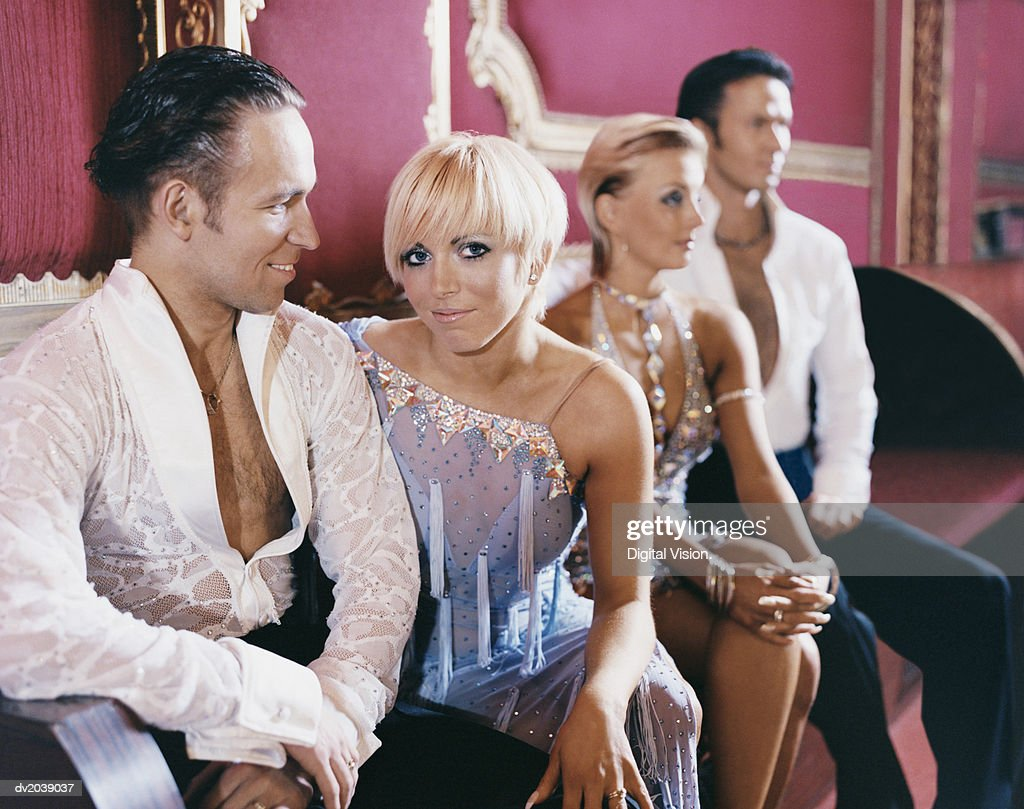 Four Well Dressed Ballroom Dancers Sitting on a Seat : Stock Photo
