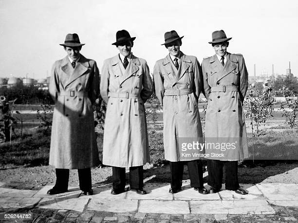 Four well dressed businessmen line up for a snapshot in front of an industrial background mid 20th century