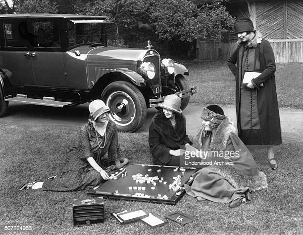 Four well dressed young women playing mahjong outdoors on a lawn California 1924