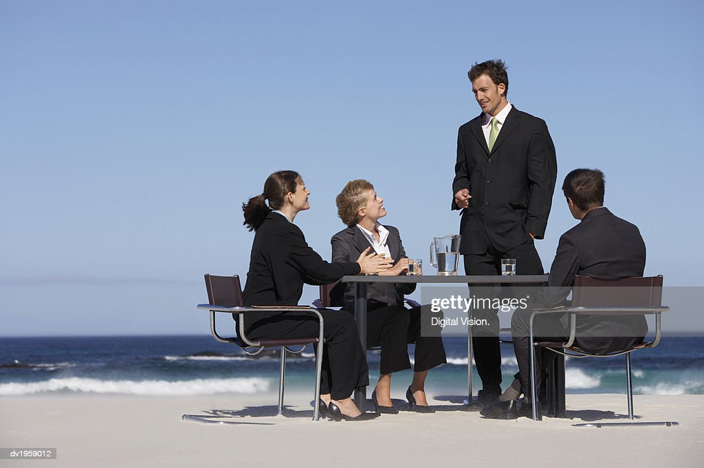 Four Well-Dressed Businessmen and Businesswomen Sit at a Table on a Beach, Having a Meeting : Stock Photo