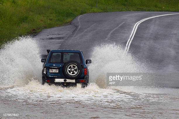 A four wheel drive braves a flooded bridge at Rocklea west of Brisbane on January 10 2011 Flash floods ripped through northeast Australia killing at...