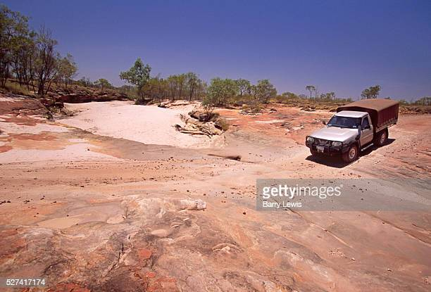 Four wheel drive vehicle crossing the dessicated area of the Bungle Bungles in Purnululu national park in the Kimberley western Australia By the side...