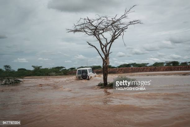Four wheel drive vehicle drives in floodwaters after a heavy rainy season downpour as they seek to fill sandbags at the Dadaab refugee complex, in...