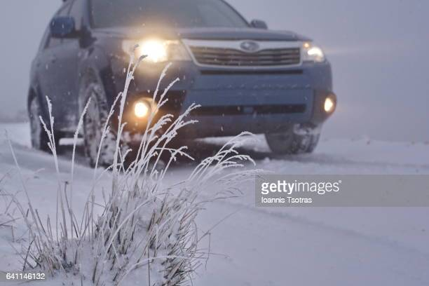 four wheel drive vehicle with lights on, on snow-covered terrain