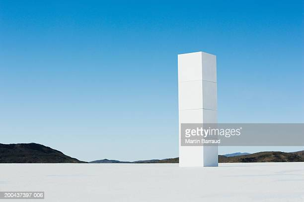 Four white cubes stacked on platform overlooking landscape
