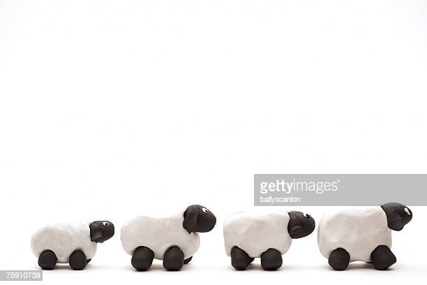 Four white sheep made of clay on a white background