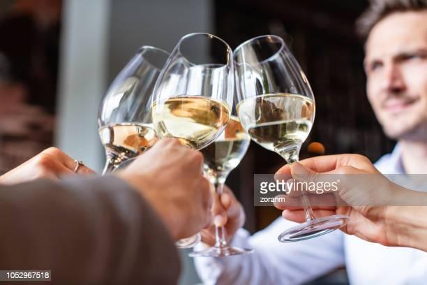 quattro bicchieri da vino bianco in un brindisi - lunch foto e immagini stock
