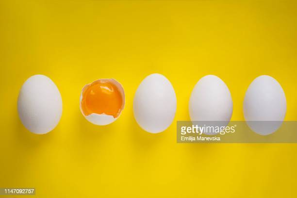 four whole eggs and one broken egg on yellow background - ei stock-fotos und bilder