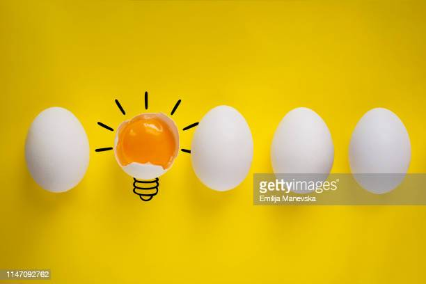 four whole eggs and one broken egg on yellow background - cholesterol stock pictures, royalty-free photos & images