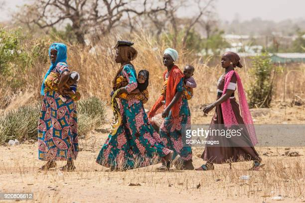 Four women and their babies walk near to the football pitch at TimTooni Football Club, just outside Tamale in Northern Ghana. Along with football...