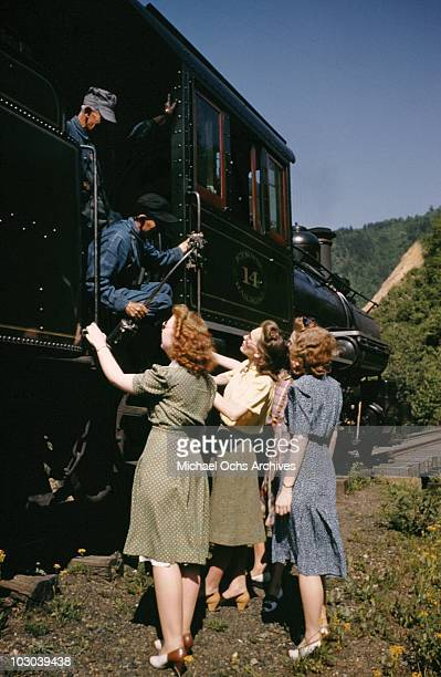 Four women chat with the engineers of the vintage narrow guage steam engine on the East Tennessee Western North Carolina railway running the 65 miles...