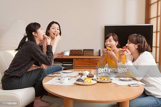 Four women eating cake