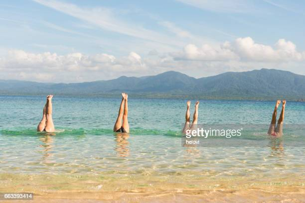 Four women handstand in turquoise sea