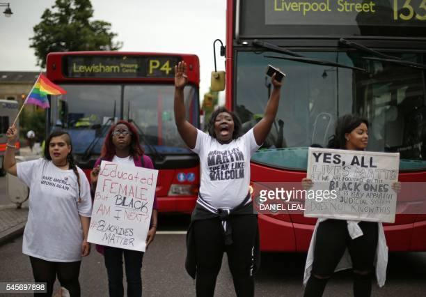 Four women hold placards and chant as protesters block the road in Brixton south London as they protest against police brutality in the US on July 9...