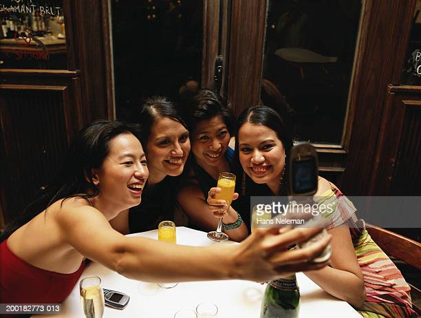 Four women in bar taking picture with camera phone