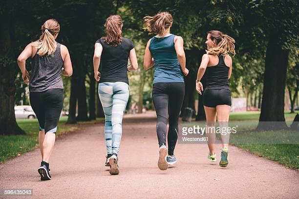 Four women jogging in park