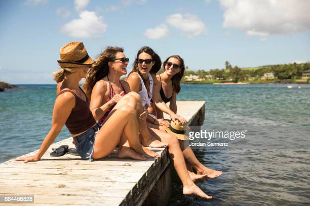 Four women laughing on a dock.