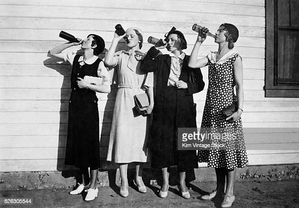 Four women line up along a wall and chug bottles of liquor in the 1920s