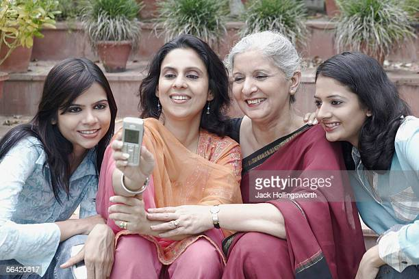 Four women looking at a mobile phone