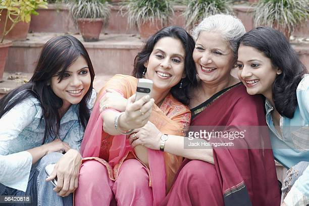 four women looking at a mobile phone - salwar kameez stock pictures, royalty-free photos & images