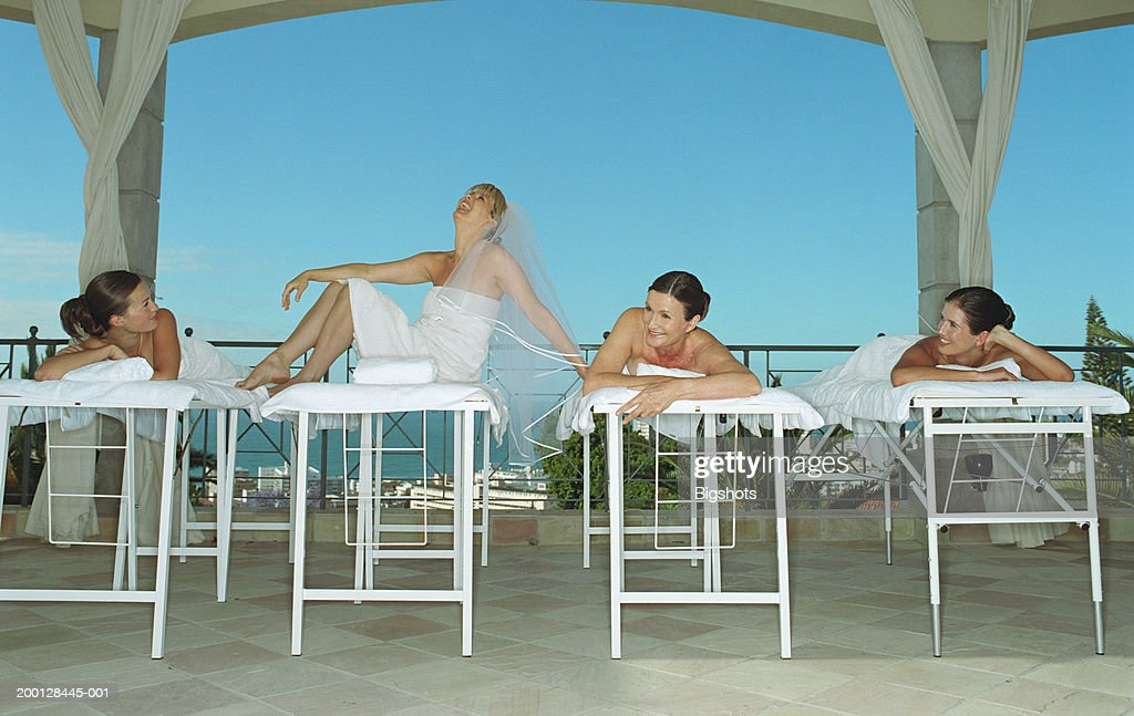 Four women on massage tables, one laughing wearing bridal veil : Stock Photo