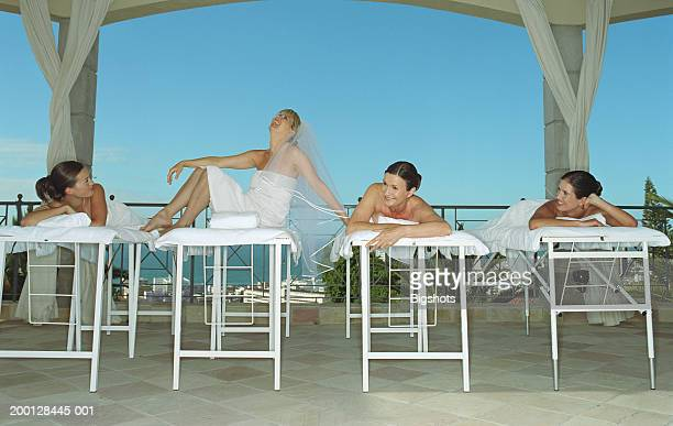 Four women on massage tables, one laughing wearing bridal veil