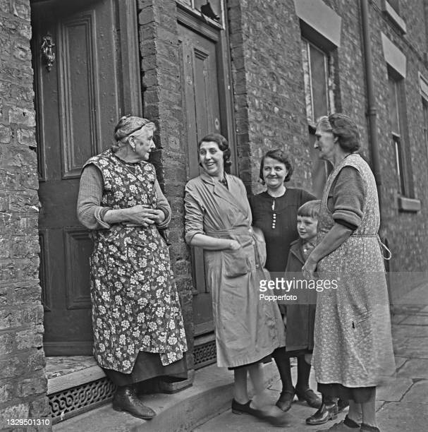 Four women, one with a young boy and three wearing housecoats, stand and chat on the doorstep of a terraced house on a residential street in...