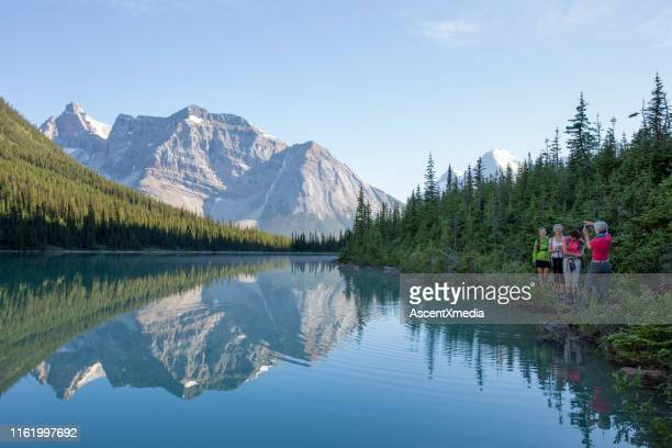 four women pause to take a photo on the lakeshore in front of a lake - canadian rockies stock pictures, royalty-free photos & images