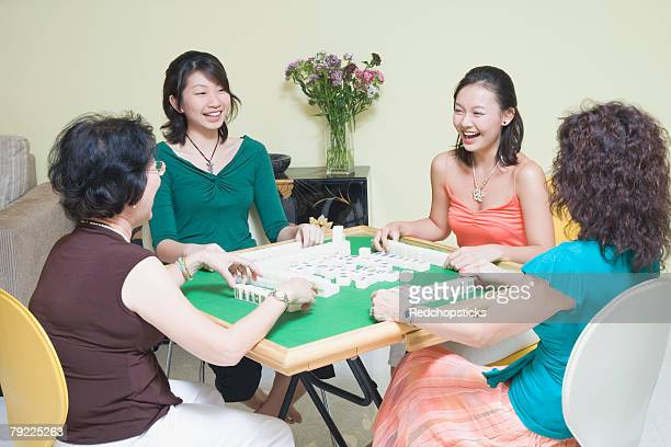 Four women playing with blocks at a table and smiling