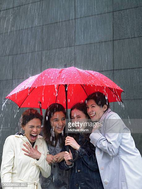Four women sharing umbrella in rain, laughing