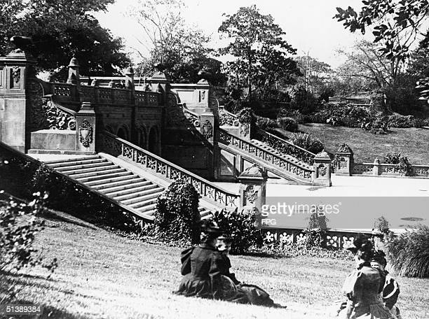 Four women sit in hats and dresses on a grassy slope adjacent to the formal stairs leading to the Bethesda Terrace in New York's Central Park early...