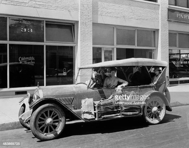 Four women sitting in an Oldsmobile with their luggage on the running board and an Airedale dog laying on top of it Portland Oregon late 1910s