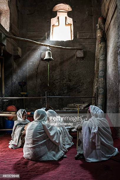 Four women sitting on the floor of a church during Orthodox Easter celebrations