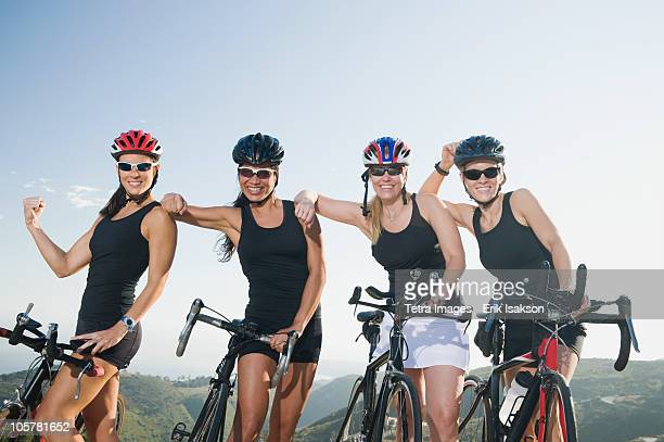Four women standing beside their bicycles